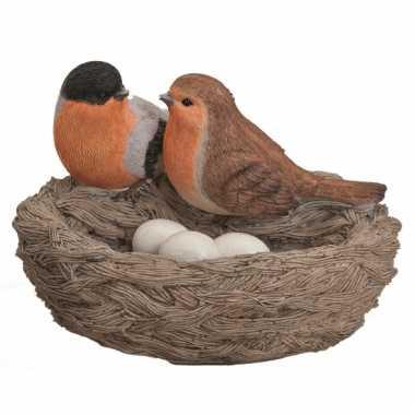 Versiering vogelnest met gekleurde vogels en eitjes oranje